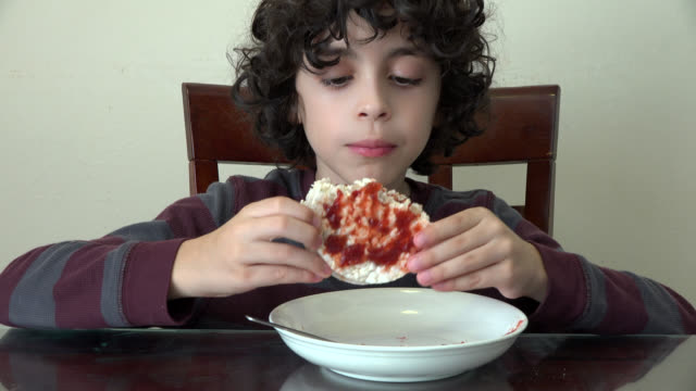 child boy eating rice cakes with marmalade - low carb diet stock videos & royalty-free footage