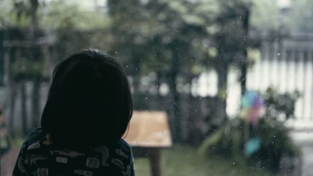 child boy look raining in the house. - boys stock videos & royalty-free footage
