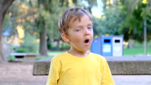 vídeos de stock e filmes b-roll de child boy looking away sitting in a park bench - bocejar