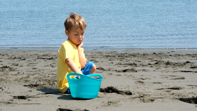 child boy playing with sand at the beach slow motion - sitting stock videos & royalty-free footage