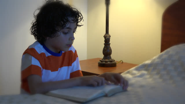 child boy reading the bible before going to sleep - vignette stock videos & royalty-free footage
