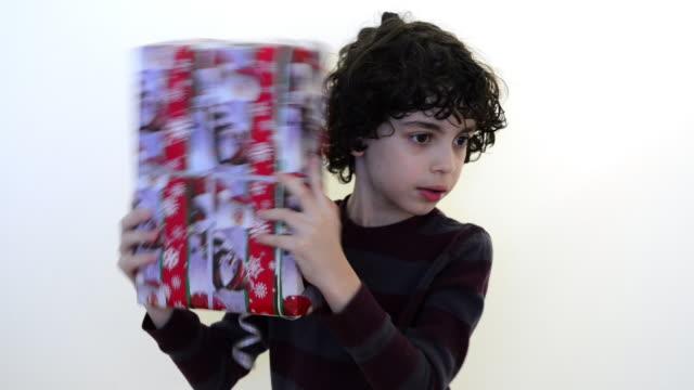 vídeos y material grabado en eventos de stock de child boy shaking a present box on a white background - sacudir