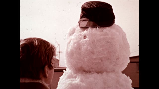 a child builds a snowman in an archival film - home movie stock videos & royalty-free footage