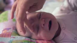 Child care concept. Mom lubricates the baby face with an allergy cream or other skin disease, a white spot on the baby skin