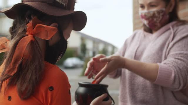covid-19パンデミック中に保護フェイスマスクでハロウィーンを祝う子供 - 菓子類点の映像素材/bロール