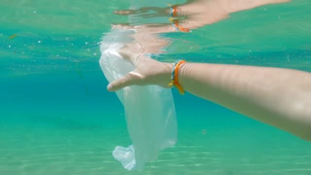 子供は海を掃除し、ビニール袋を取り除きます。環境問題 - 使い捨て点の映像素材/bロール
