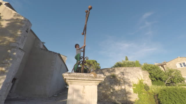 child climbing on a monument - luberon stock-videos und b-roll-filmmaterial