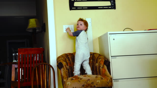 child climbing on chair flicking light switch 4k - award stock videos & royalty-free footage