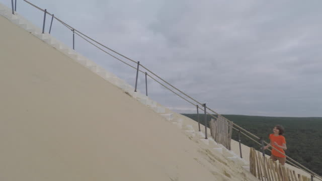 child climbs stairs on the pyla dune - dune of pilat stock videos and b-roll footage