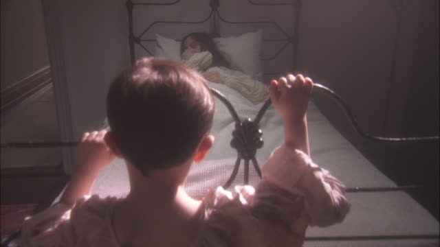 a child clutches the footboard of a bed and looks at his sick mother. - historische nachstellung stock-videos und b-roll-filmmaterial
