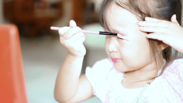 Child cosmetics little girl playing make up