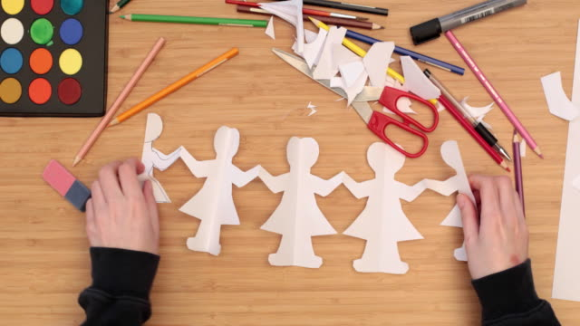 Child cutting chain fairy figures out of paper
