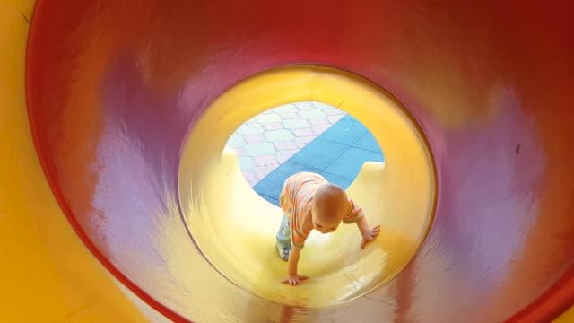 kind gefährlich stecken auf einer folie auf dem spielplatz - rutschen stock-videos und b-roll-filmmaterial