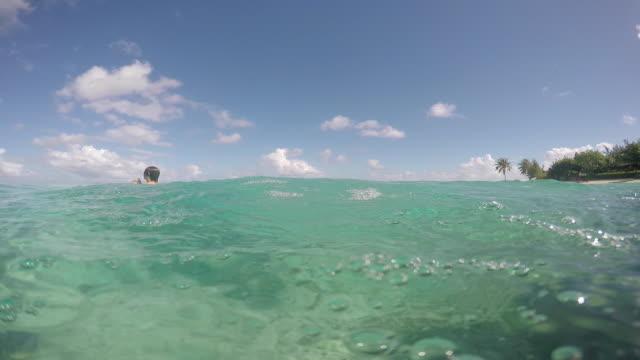 vídeos de stock, filmes e b-roll de child dives into the sea - huahine island