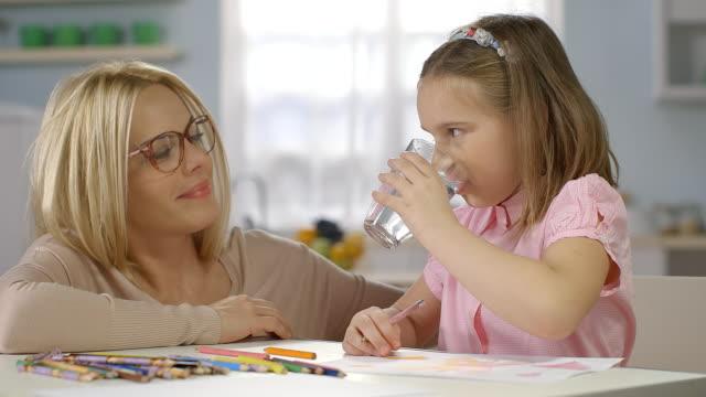 bambino facendo compiti a casa. madre dà un bicchiere di wather - acqua potabile video stock e b–roll