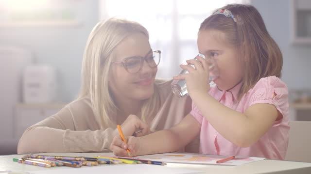vidéos et rushes de enfant faire devoirs à la maison. mère donne un verre de wather - verre d'eau
