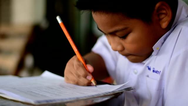 vidéos et rushes de enfant faisant des devoirs - gomme