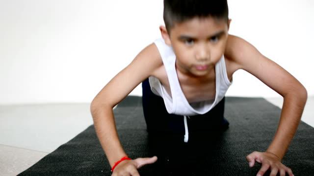 Niño haciendo flexiones en su casa