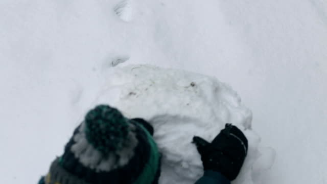 child doing snowball, making snowman, fun in snow - making a snowman stock videos & royalty-free footage