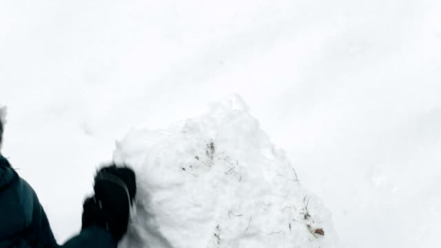 child doing snowball, making snowman, fun in snow - igloo stock videos & royalty-free footage