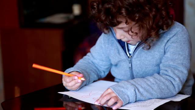 stockvideo's en b-roll-footage met kind trekt een potlood tekening op de glazen tafel - bukken