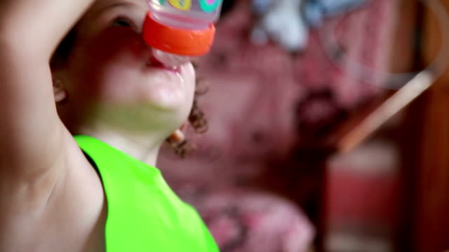 Child drinking water from baby bottle