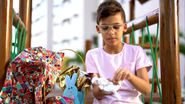 child eating chocolate easter egg - eating video stock e b–roll