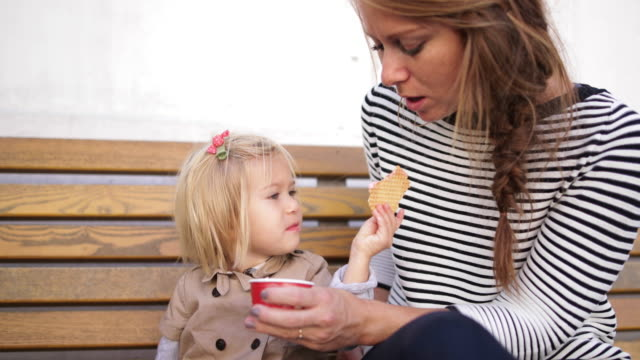 Child eating ice cream on bench with mother