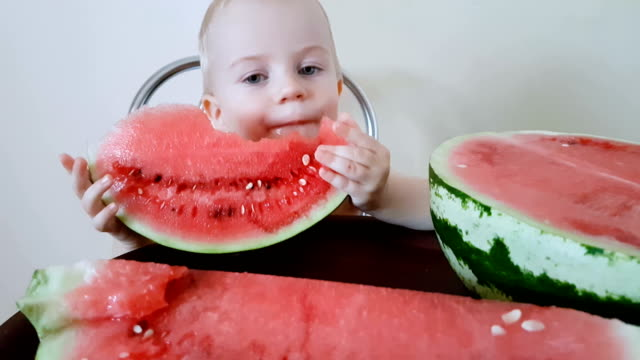 Child eats red slice of watermelon