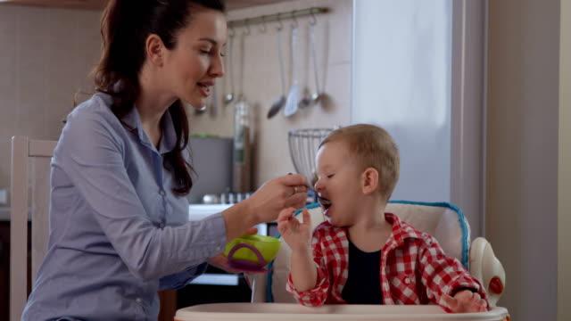 vídeos y material grabado en eventos de stock de child enjoying eating food with mother sitting in a baby chair - cuchara