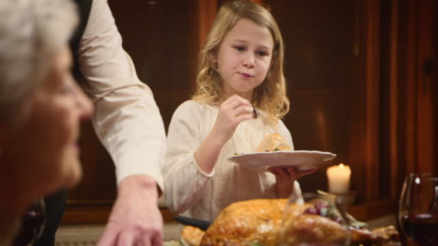 Child enjoying her Thanksgiving turkey slice her granddad served her