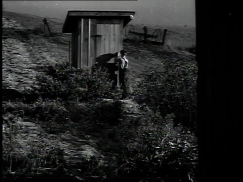 vídeos de stock, filmes e b-roll de 1940 ms child exiting outhouse / st. clairsville, ohio, united states - dependência