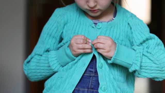 vidéos et rushes de child fastening buttons - 4 5 ans