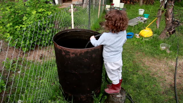 child filling up the big metal barrel with water - water conservation stock videos & royalty-free footage