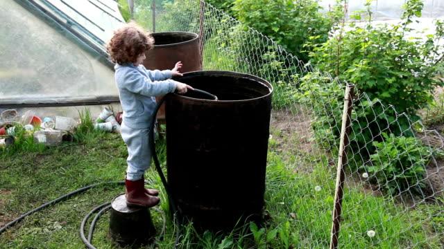vídeos y material grabado en eventos de stock de niño llenando el barril metálico grande con agua - llenar