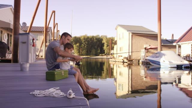 vídeos de stock e filmes b-roll de filho pesca para baixo - barco casa
