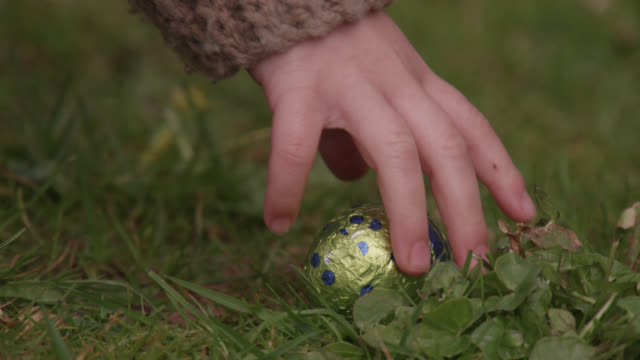 Child gathers chocolate during easter egg hunt, Bristol, England