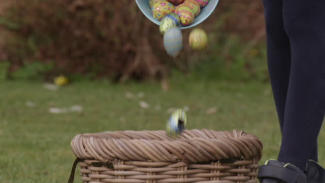 child gathers chocolate during easter egg hunt, bristol, england - happy easter stock-videos und b-roll-filmmaterial