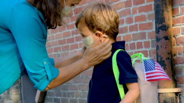 child getting ready to go to school in pandemic times - educazione video stock e b–roll