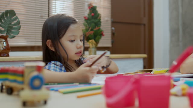 child girl doing homework and drawing on table in living room - 4 5 years stock videos & royalty-free footage