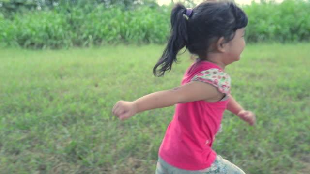 vidéos et rushes de fille enfant qui traverse le parc, le mouvement lent - série d'émotions