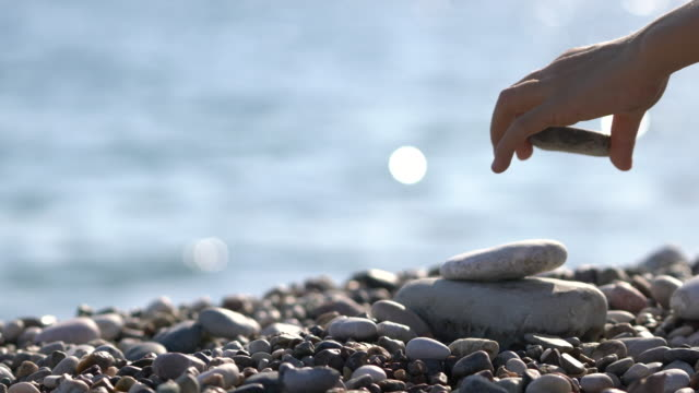child hand balancing stack of stones on beach - roccia video stock e b–roll