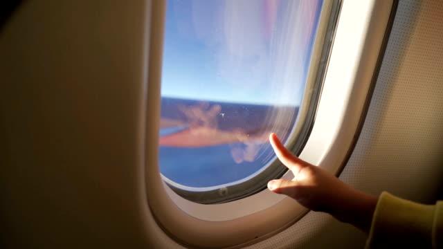 kinderhand, die auf das flugzeugfenster zeigt. - passagierflugzeug stock-videos und b-roll-filmmaterial