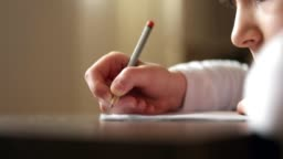Child hand using pencil to practice writing on a book.