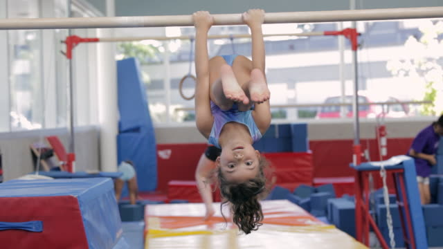 WS child hanging upside down on gymnastics bar / Vancouver, British Columbia, Canada