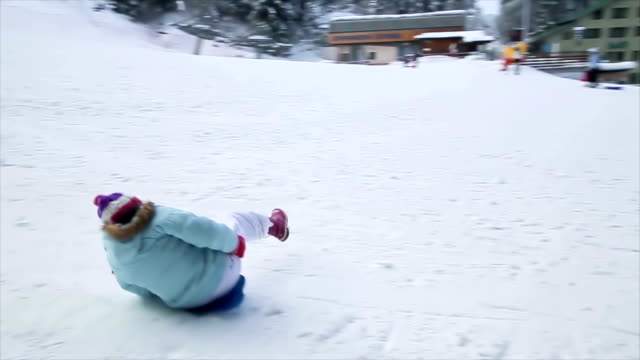 Child have fun with toboggan in winter ski center