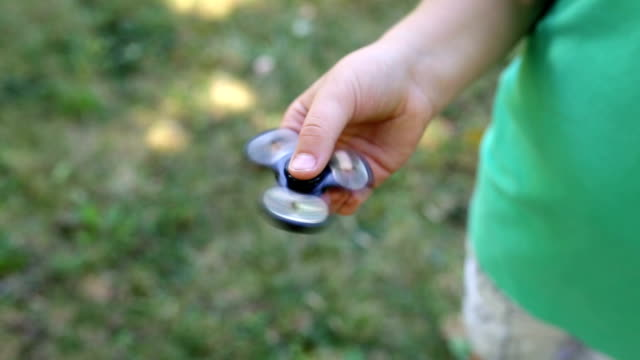 child having fun outdoors with fidget spinner - wheel stock videos and b-roll footage