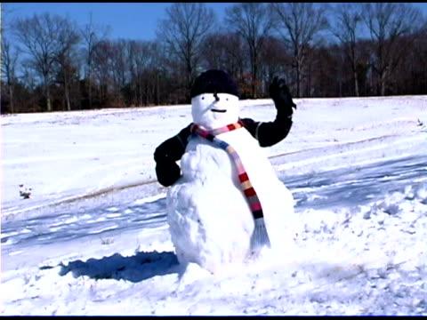 child hiding behind snowman and waving - schneemann stock-videos und b-roll-filmmaterial