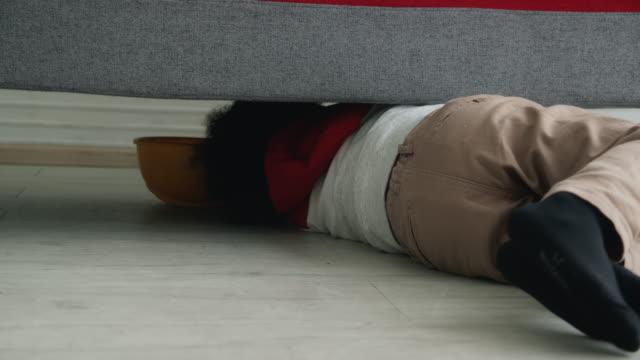 vídeos de stock, filmes e b-roll de criança escondida debaixo do sofá na sala de estar. tiro de mão sincero. - esconder