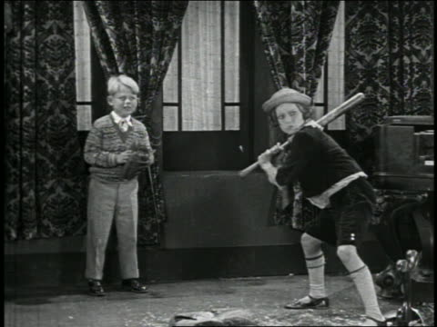 b/w 1928 child hitting baseball in living room / boy catcher in background / short - 1928 stock videos & royalty-free footage